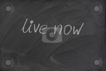Live now phrase on blackboard stock photo, Live now phrase handwritten with white chalk on blackboard with strong patterns of eraser smudges by Marek Uliasz