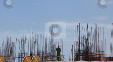 Construction worker with steel rebar stock photo, View of construction worker with hardhat on jobsite surrounded by rebar by Jill Reid
