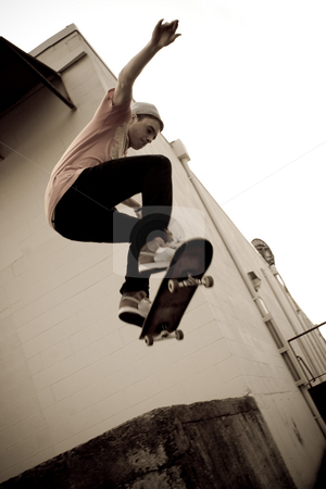 Skateboarding Jump stock photo, A young skateboarder launches off a concrete loading dock in an urban setting. by Todd Arena
