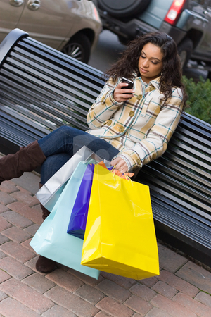 Shopper With Mobile Phone stock photo, An attractive young woman checking her cell phone while out shopping in the city.  She might be texting or surfing the internet. by Todd Arena