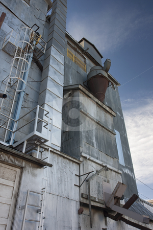 Industrial background - old grain elevator against sky stock photo, Industrial background - a metal exterior of old grain elevator with pipes, ducts, ladders and chutes against sky by Marek Uliasz