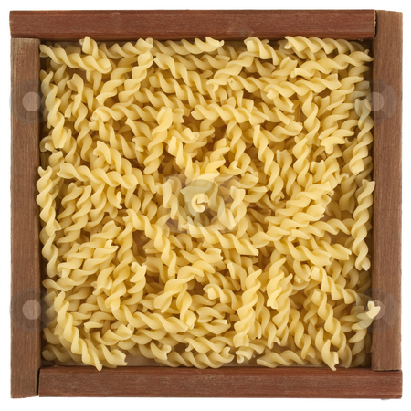 Uncooked fusilli pasta in wooden box stock photo, Uncooked fusilli pasta in a rustic wooden box or frame isolated on white by Marek Uliasz