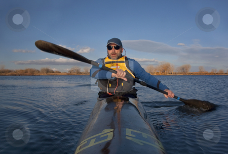 Mature paddler in a narrow racing kayak stock photo, Mature paddler exercising in a narrow carbon fiber racing kayak on a lake in early spring in Colorado, thirteen - temporary race number placed on deck by myself by Marek Uliasz