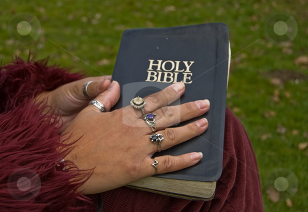 Closeup with a Woman's Hand on a Bible stock photo, Closeup of a woman's hand with many rings on a worn black Holy Bible.  Darker skin hand wearing burgundy clothing. by Valerie Garner