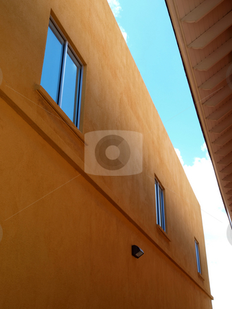 Contemporary two story stucco building and windows stock photo, Contemporary stucco building with bue sky reflected in windows by Jill Reid