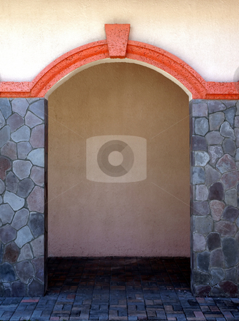 Stone pillars and colorful archway stock photo, Stone pillars and colorful archway through a stucco building by Jill Reid