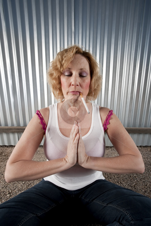 Smoking woman meditating stock photo, Woman meditating with cigarette in front of corrugated metal by Scott Griessel