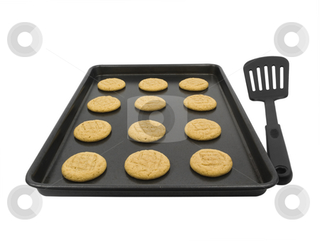 Peanut butter cookies stock photo, Peanut butter cookies on baking pan with spatula by John Teeter