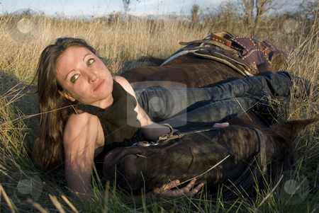 Woman and horse in field stock photo, Young woman and her blackhorse laid down in a field by Bonzami Emmanuelle