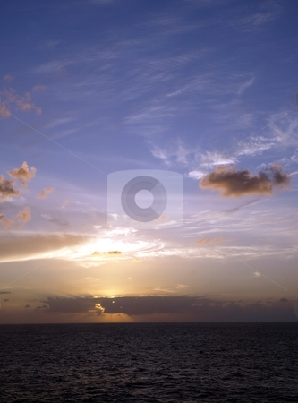 Bright blue sky gives way to dramatic ocean sunset stock photo, Sunset colors the sky and ocean on a cloudy horizon by Jill Reid