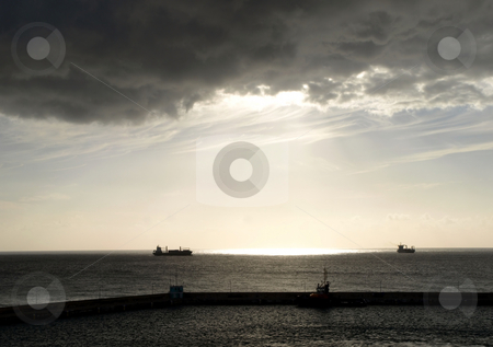 Brooding sky follows freighters at sea stock photo, A grey and brooding sky shines sunlight on the ocean and freighters passing on the sea by Jill Reid