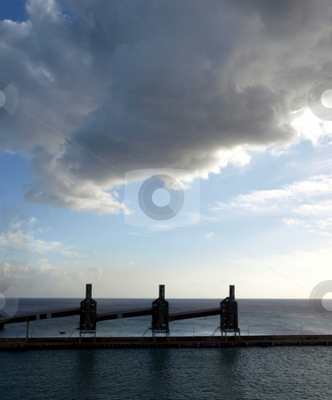 Dark cloudy sky over silos in Barbados stock photo, Sun sets through a dark cloudy sky and silhouettes of silos on Barbados dock by Jill Reid
