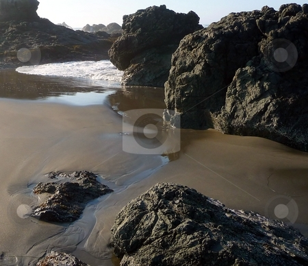 Small riptide on rocky beach stock photo, Small riptide moves along the sand on a rocky beach in Oregon by Jill Reid
