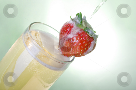 Pouring champagne with Strawberry stock photo, Pouring champagne with strawberry over light green background by iodrakon