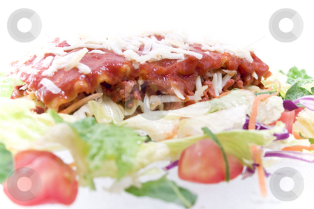 High key Close up shot of Lasagna stock photo, High key Close up shot of Lasagna with salad - selective focus on center by iodrakon