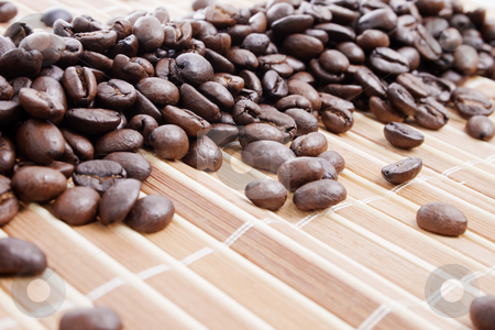 Coffee beans on bamboo placemat stock photo, Coffee beans on bamboo placemat - focus on center by iodrakon