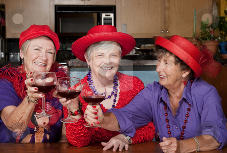 Three red hat ladies toasting with wine stock photo, Three red hat ladies toasting with big wine glasses by Scott Griessel