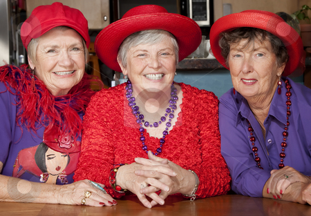 Three Senior Women Wearing Red Hats stock photo, Three friendly senior women wearing red hats by Scott Griessel