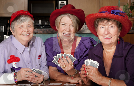 Ladies wearing red hats playing cards stock photo, Ladies wearing red hats playing a hand of cards by Scott Griessel