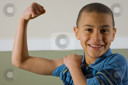 9 Year Old Multi Racial Boy Showing Off His Muscles stock photo, Cute 9 year old multi racial boy is proudly showing off his muscles while giving a winning smile. by Valerie Garner