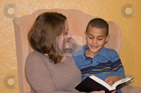 Mother and Son Enjoying A Book Together stock photo, A young mother is enjoying time together with her bi-racial awesome son reading a book.  This family time is precious to both. by Valerie Garner