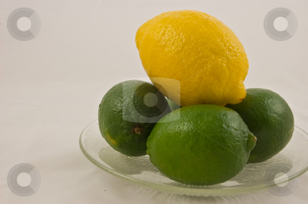Fresh Limes and One Lemon on Glass Plate stock photo, Fresh green limes and one yellow lemon on a clear glass plate are isolated against a white background. by Valerie Garner