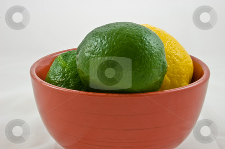 A Red Bowl of Limes and One Lemon stock photo, This closeup is a shot of a red bowl of green limes and one yellow lemon, isolated on a white background. by Valerie Garner