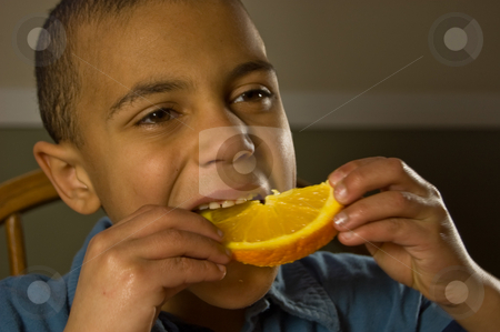 Multi Ethnic Boy Eating an Orange stock photo, Closeup photo of a beautiful multi ethnic boy eating a juicy orange slice for a healthy snack. by Valerie Garner