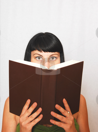 Young woman reading a book. stock photo, An pretty black haired girl reading in an big book. by Horst Petzold