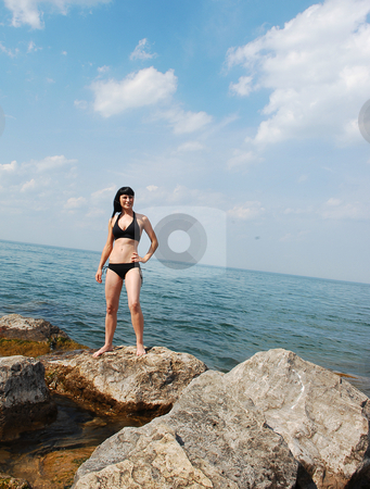 Bikini model on the beach. stock photo, Young beautiful bikini girls standing on big rocks on the beach of lake Ontario by Horst Petzold