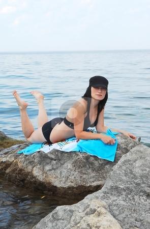 Bikini model on the beach. stock photo, Young beautiful bikini girl lying on her stomach on big rocks on the beach of  lake Ontario. by Horst Petzold