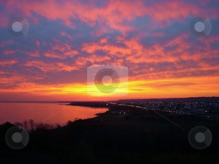 Sunrise    stock photo, Sunrise over the lake Ontario early in the morning with bright yellow sky and dark clouds. by Horst Petzold
