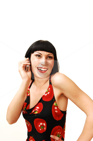 Standing woman on the cell phone. stock photo, A young pretty woman standing in a studio and having fun talking on the cell phone for white background in a tomato print dress. by Horst Petzold