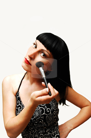 Young woman putting make-up on. stock photo, An young pretty girl in a black and white dress putting new make-up on, standing in an studio for white background. by Horst Petzold