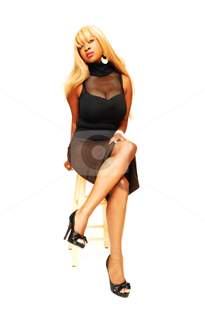Young Jamaican girl sitting. stock photo, An busty young Jamaican girl in a black top and brown skirt, long blond hair  sitting on a bar chair in an studio for white background. by Horst Petzold