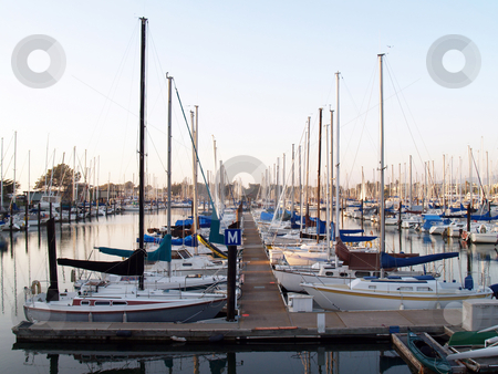 Sailboats tied up in berths in marina stock photo, Dock at marina with boats in berths by Jeff Cleveland