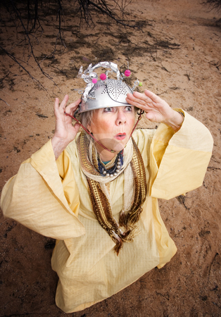 Waiting for the Mother Ship stock photo, Crazy woman wearing a colander helmet waiting for a spaceship by Scott Griessel
