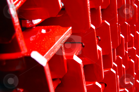 Stacked red metal support beams stock photo, Close up of a stack of painted red metal support beams for scaffolding / construction by Chris Alleaume