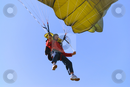 Parachutist stock photo, Parachutist pulling brakes of a green parachute. by Ivan Paunovic