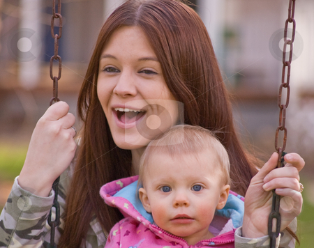 Young Mother and Baby Daughter on Swings stock photo, Young mother is laughing while swinging with baby daughter in a family moment of fun. by Valerie Garner