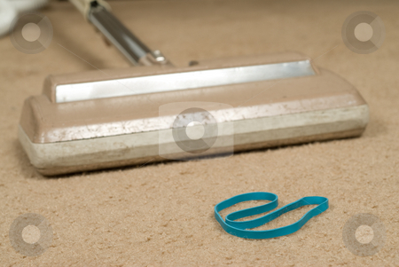 Sucking Up An Elastic stock photo, Closeup view of an elastic band in the way of a vacuum cleaner by Richard Nelson