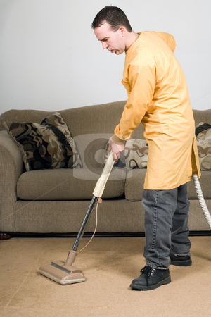 Vacuuming stock photo, A man wearing a work coat and vacuuming the carpets inside a house by Richard Nelson