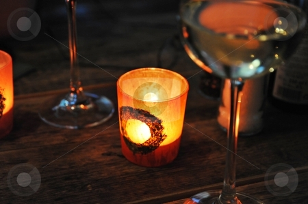 Candlelight stock photo, Lit candle on wood table with glasses by Jaime Pharr