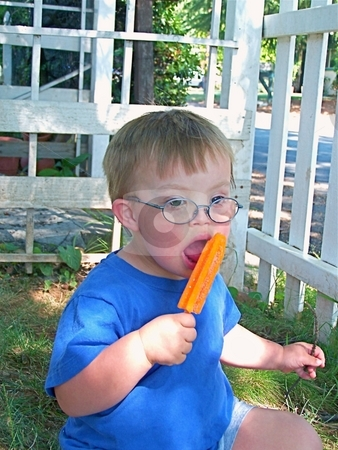 Bow with Downs Syndrome eating  a popsicle. stock photo, Boy with Downs Syndrome eating a popsicle by Gregory Dean
