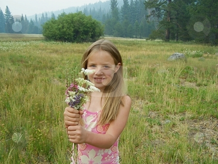 Girl in a field holding flowers stock photo, Young girl in a field holding flowers. by Gregory Dean