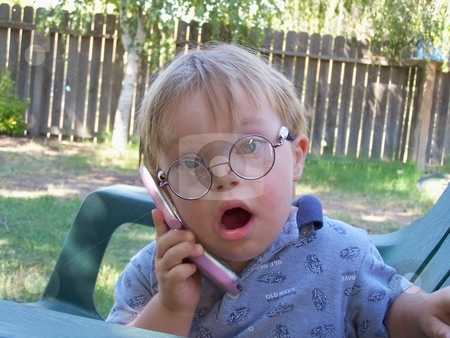 Little boy talking on phone stock photo, Little boy with Downs Syndrome talking on the phone. by Gregory Dean