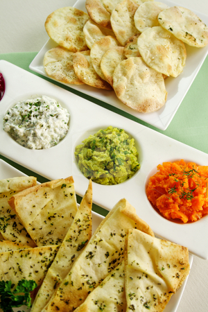 Assorted Dips stock photo, Assorted dips of carrot, cottage cheese and herbs, pea and basil with pita crisps. by Brett Mulcahy