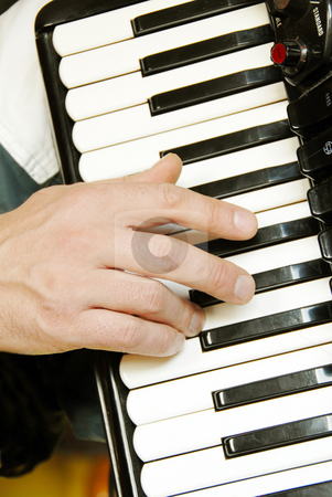 Musician hand playing accordion stock photo, Musician hand playing accordion closeup in dramatic shadows by Julija Sapic