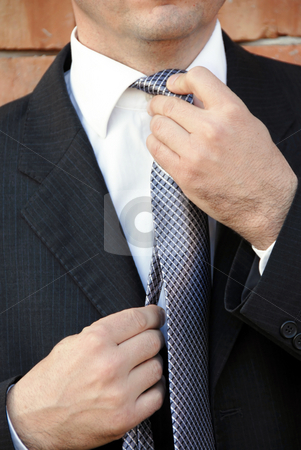 Businessman adjusting necktie stock photo, Mature businessman in suit adjusting his necktie by Julija Sapic