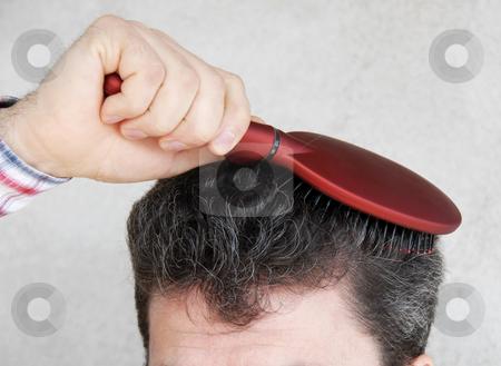 Man brushing hair stock photo, Mature man brushing black greyish hair with red hairbrush by Julija Sapic